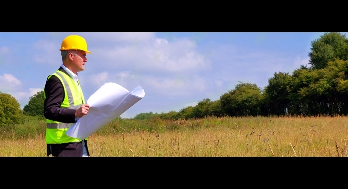 Man wearing a hard hat, walking through a field